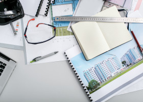 Maps, notebook, ruler and pens lie on office table